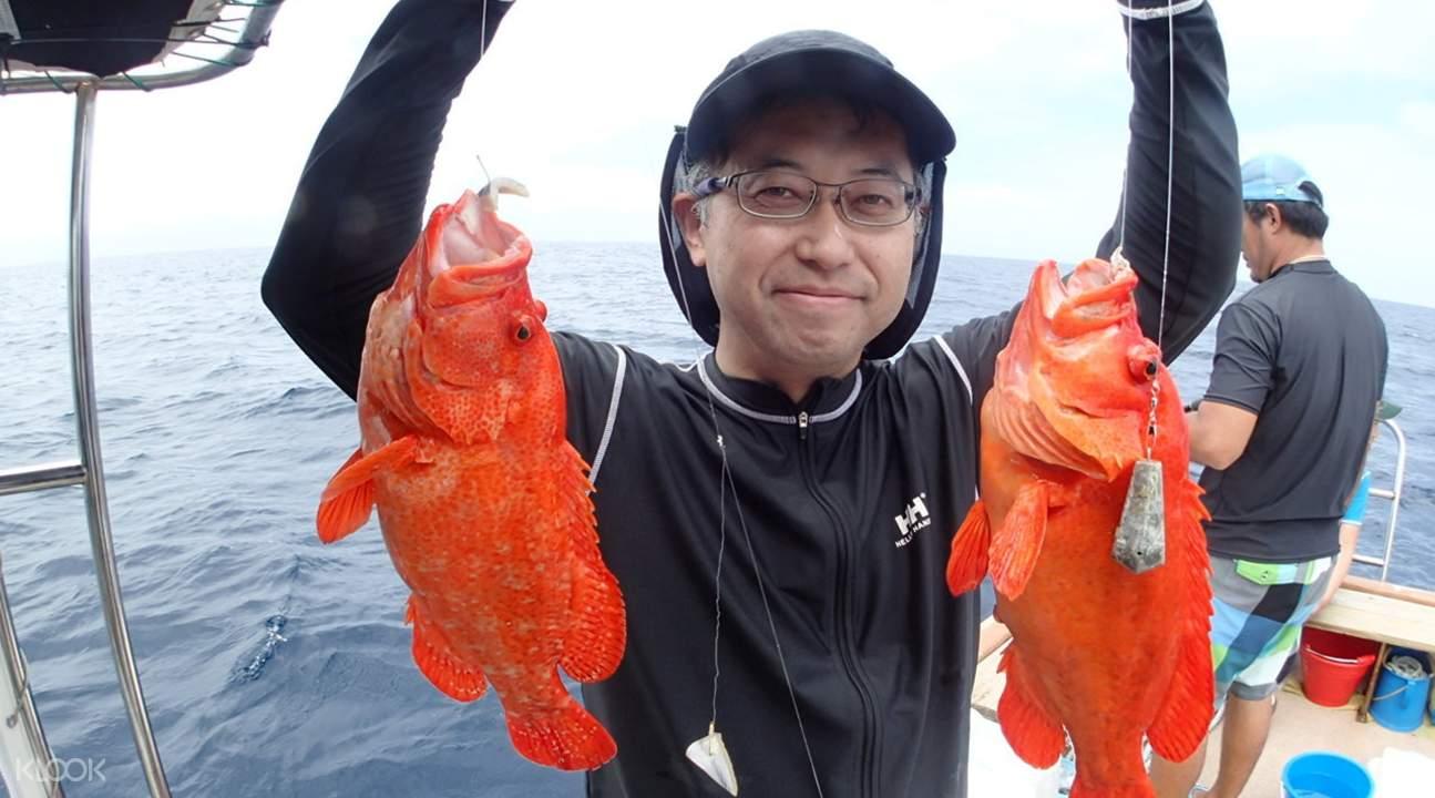 man holding two orange fish next to ishigaki island