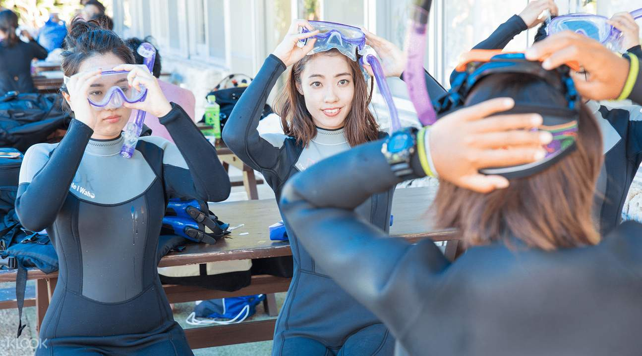 three women putting on snorkeling gear in the blue cave, okinawa