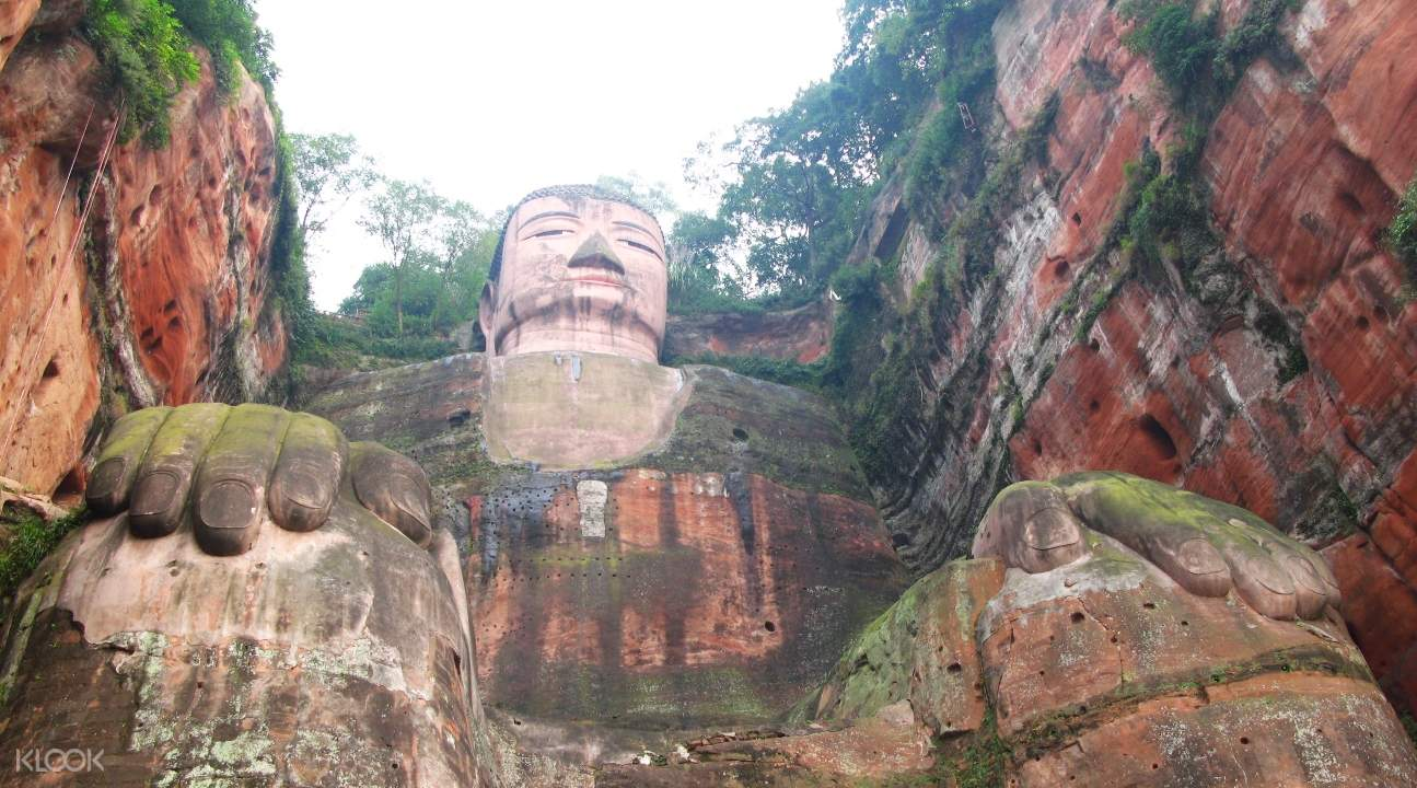 a view of the famous Leshan Giant Buddha from below; its sits in between two cliff faces