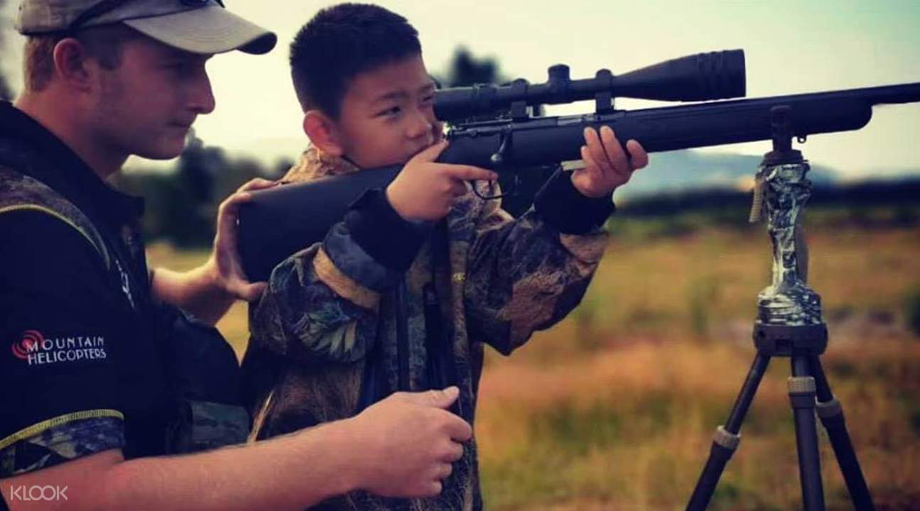 trainer from the southern hunting adventures teaching a young boy how to aim an ak-47