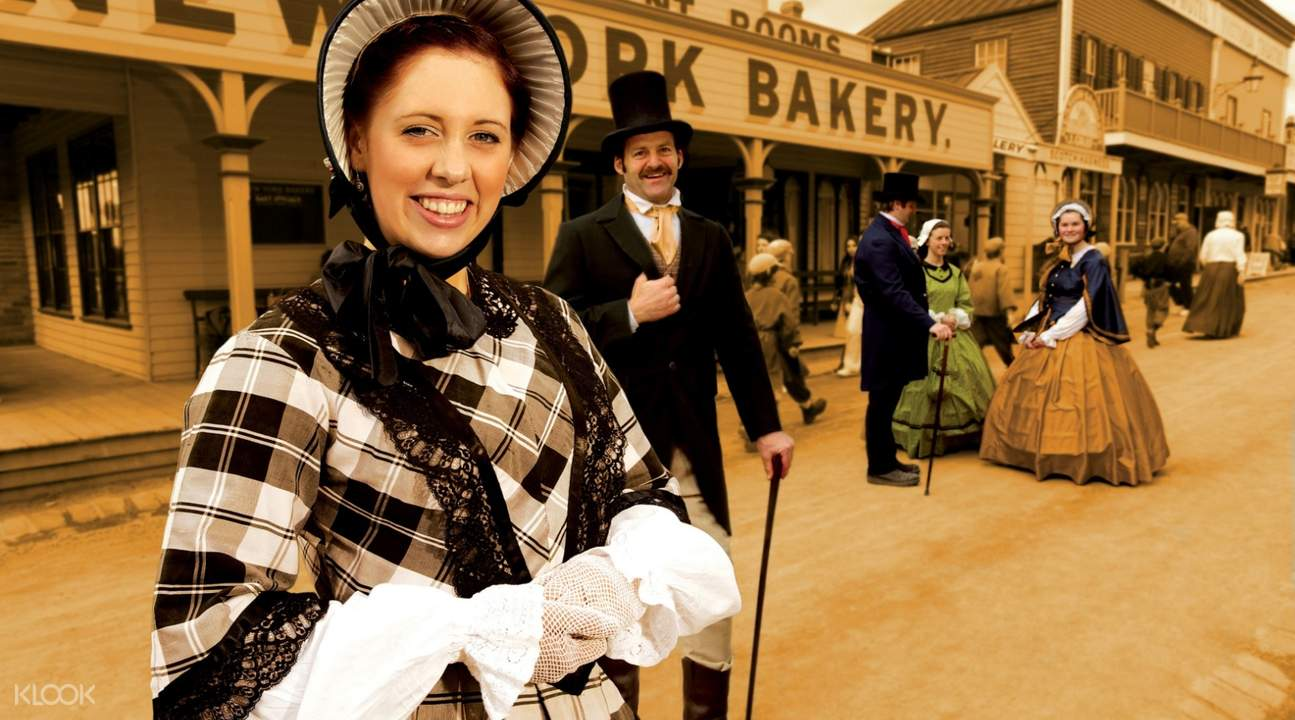 people in costume standing next to houses in sovereign hill australia
