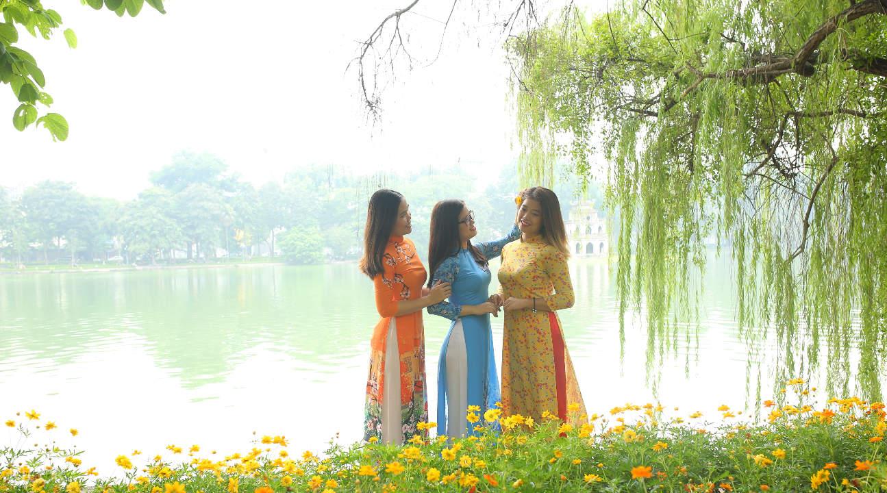 women wearing ao dais posing by a lake
