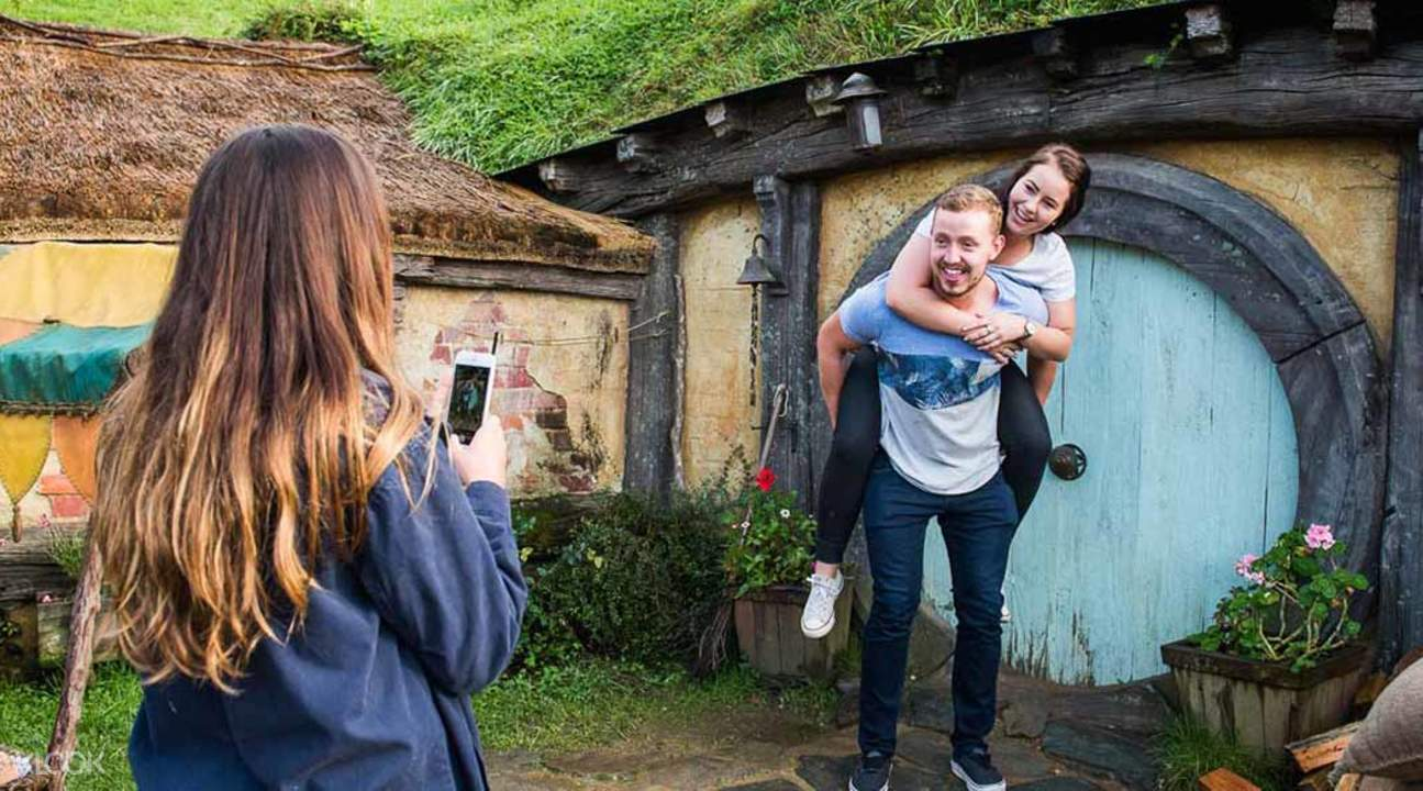 man carrying woman while taking picture at hobbiton movie set