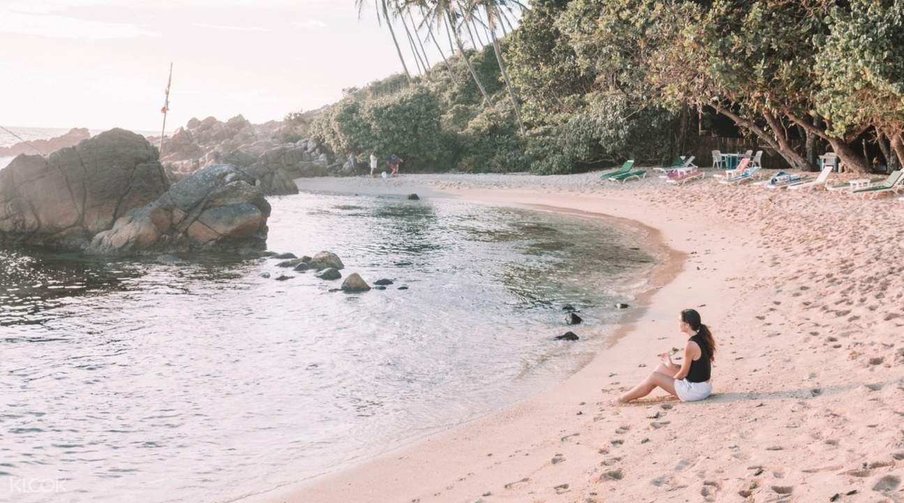woman sitting on sands in mirissa beach sri lanka