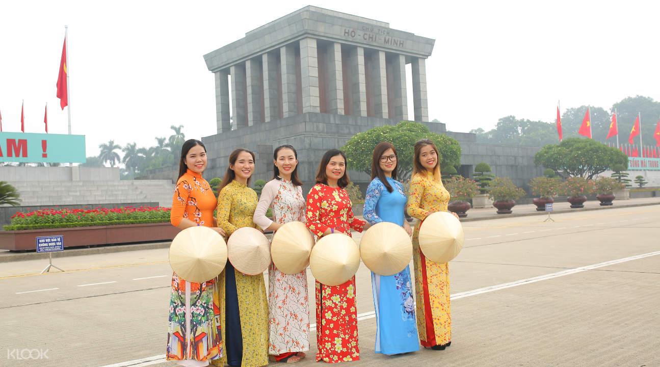 women wearing ao dais while carrying conical hats near the Ho Chi Minh Mausoleum
