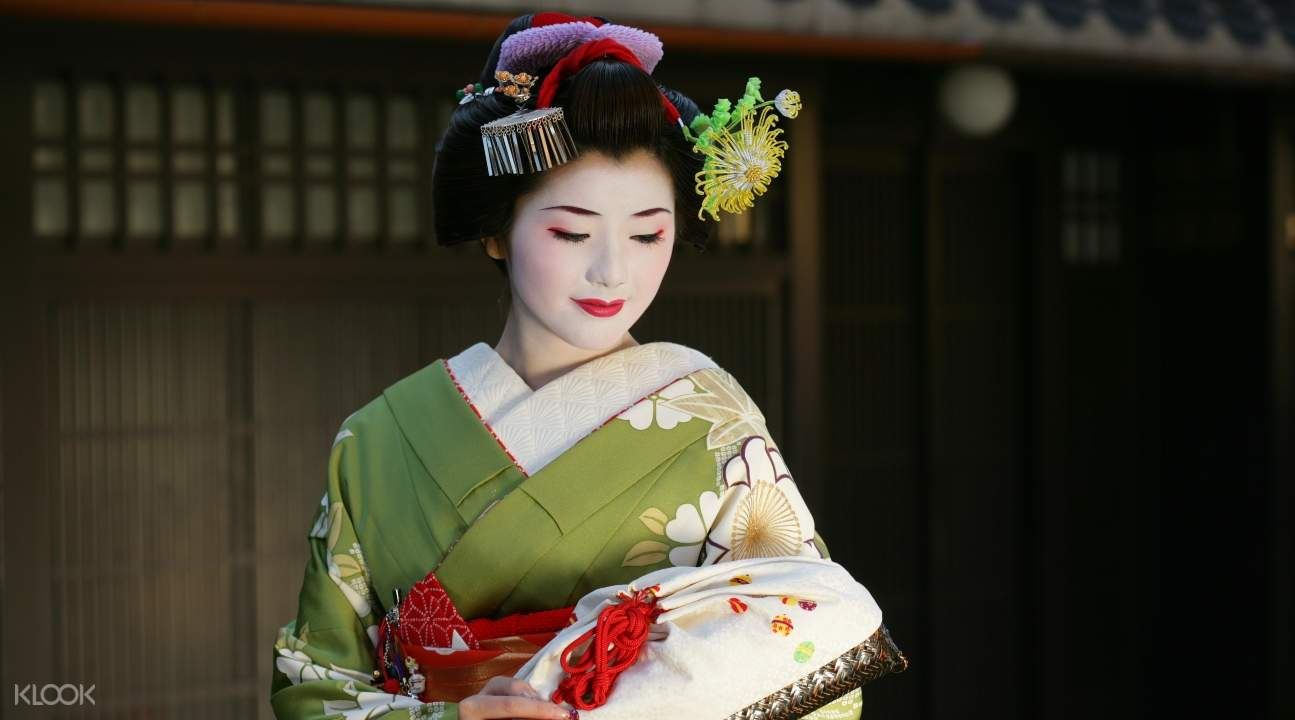 a maiko in a light green kimono carrying a purse
