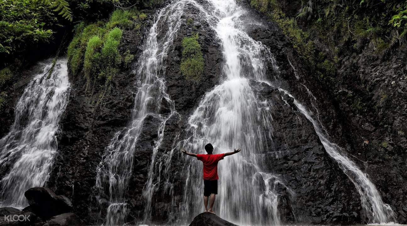 man posing in front of Curug Sawer Waterfall
