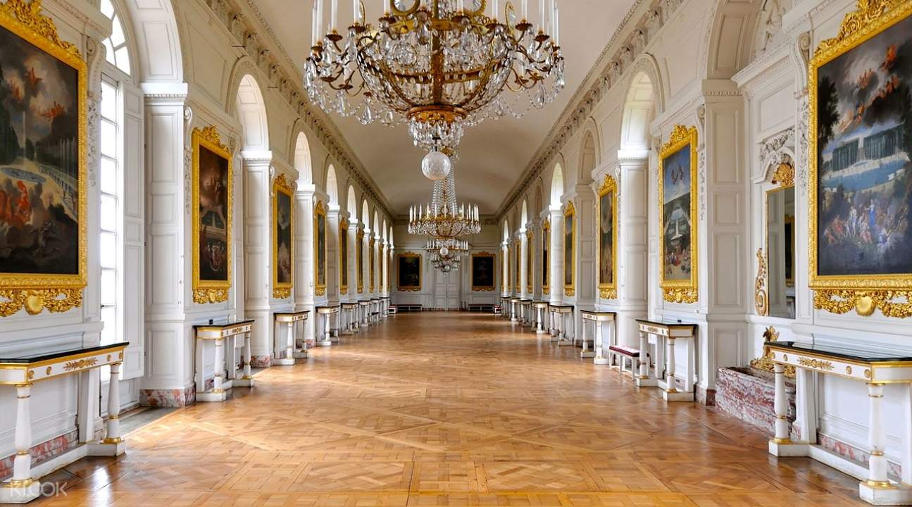 a hall inside Versailles; there are paintings on the side