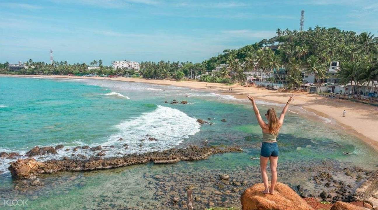 woman standing next to mirissa beach with waves
