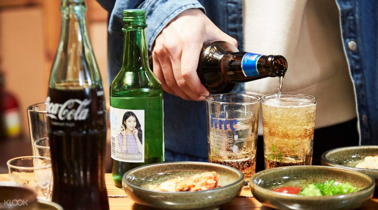 man pouring korean beer in glass