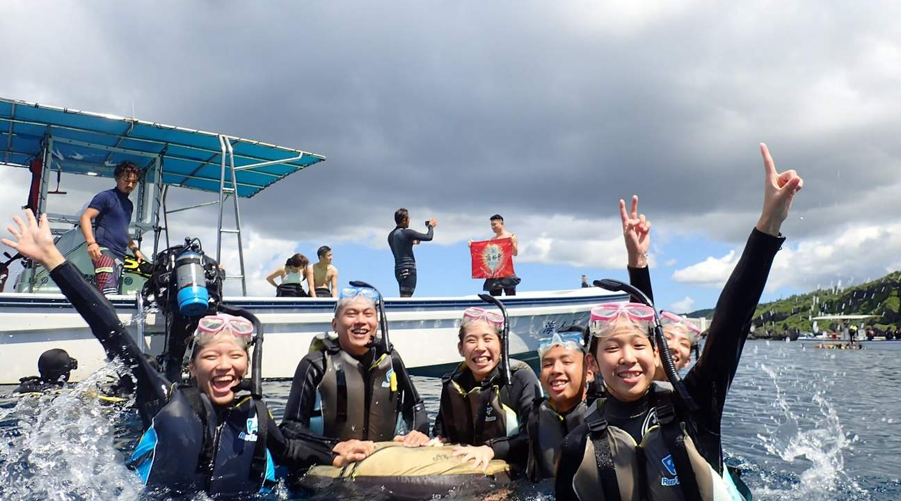 divers and snorkelers next to boat in okinawa sea