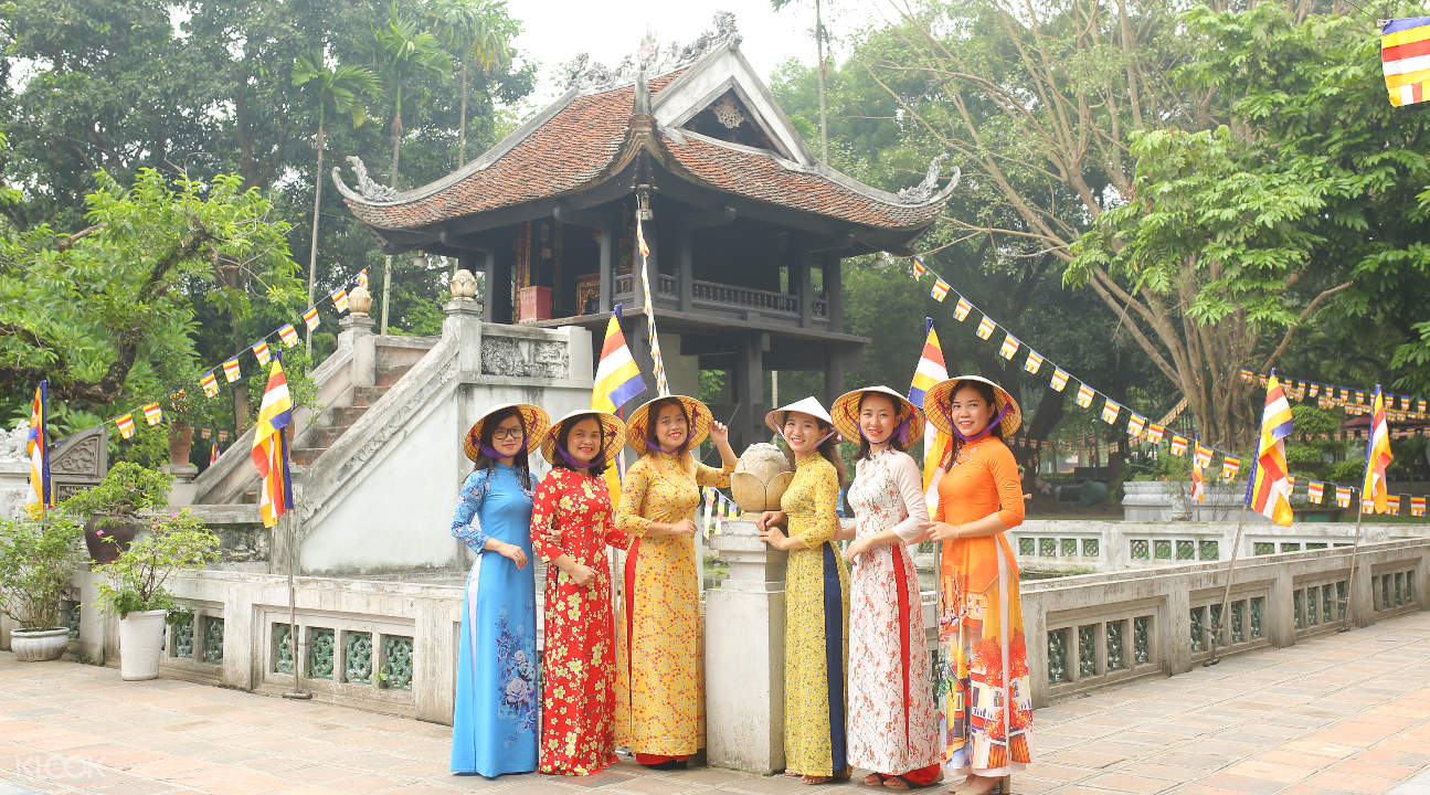 women wearing conical hats and ao dais in front of a temple