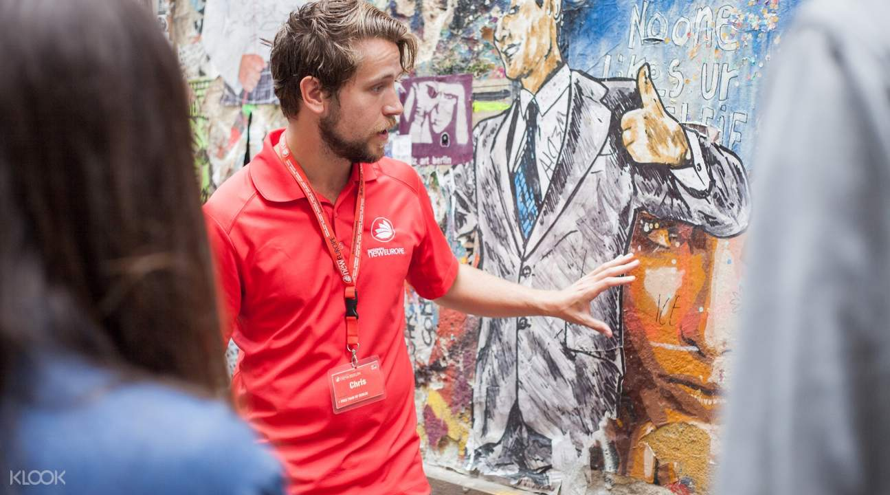 tour guide pointing at street art in berlin