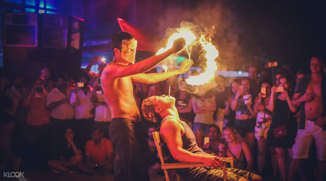 fire dancer interacting with party goer at Full Moon Party