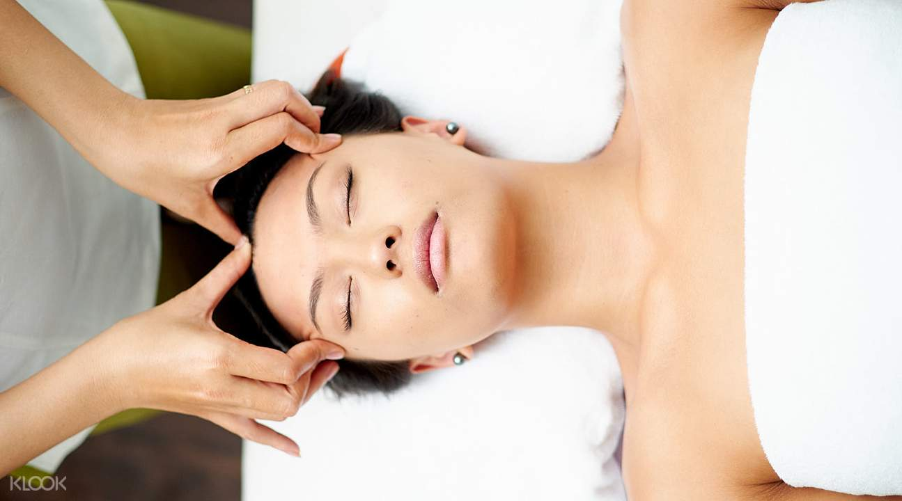 woman lying down and receiving a facial massage