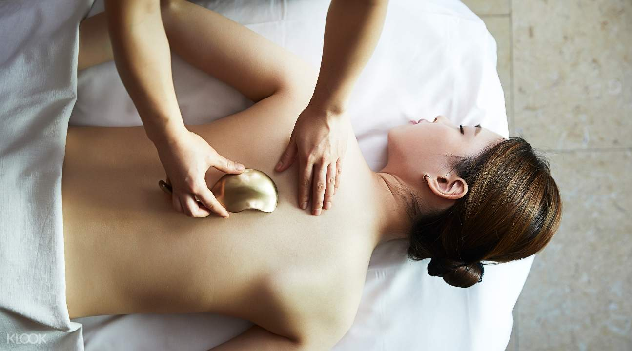 woman getting a body massage; the masseuse is using a Korean bronze implement