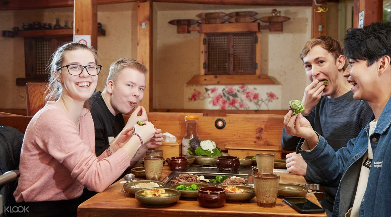 foreigners eating at a local korean restaurant with locals