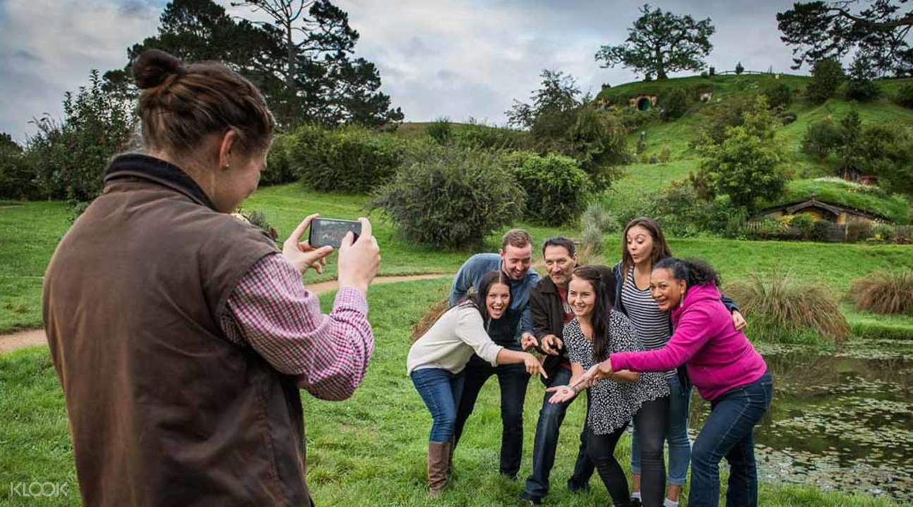 group of friends taking picture at hobbiton movie set