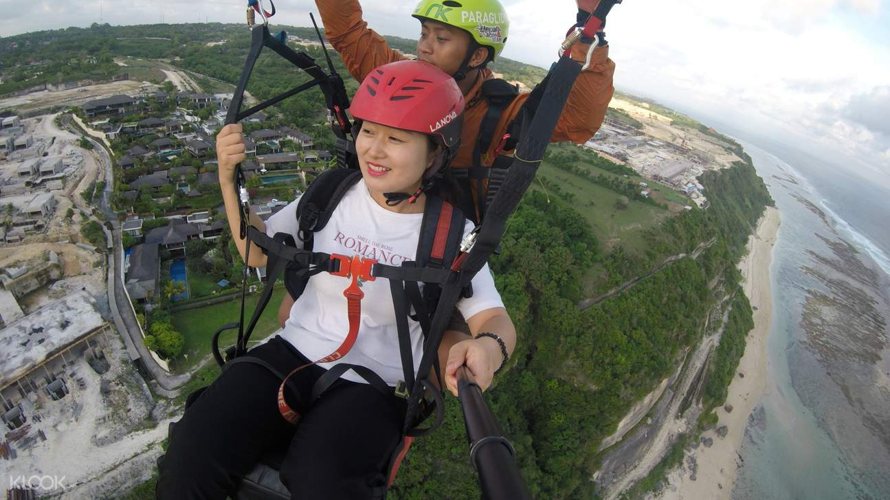 woman and man forming a heart with their hands while paragliding