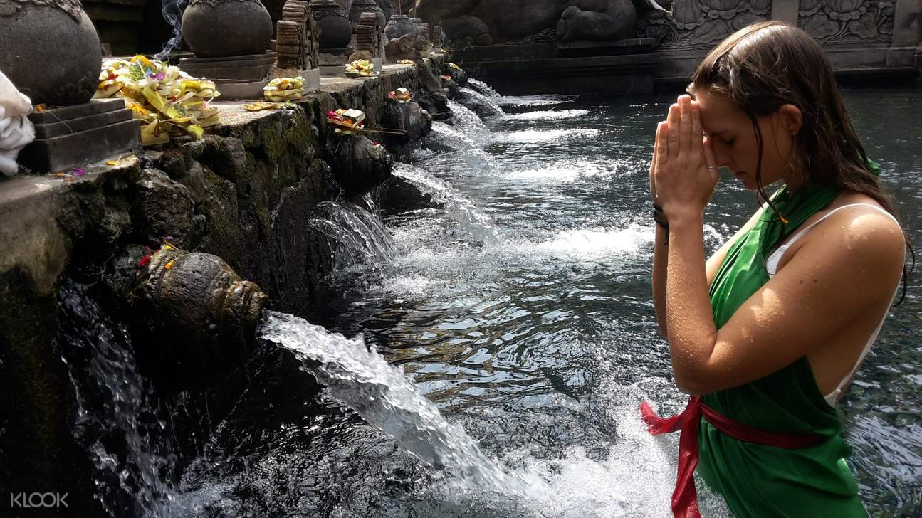 woman praying while at the holy bath in bali