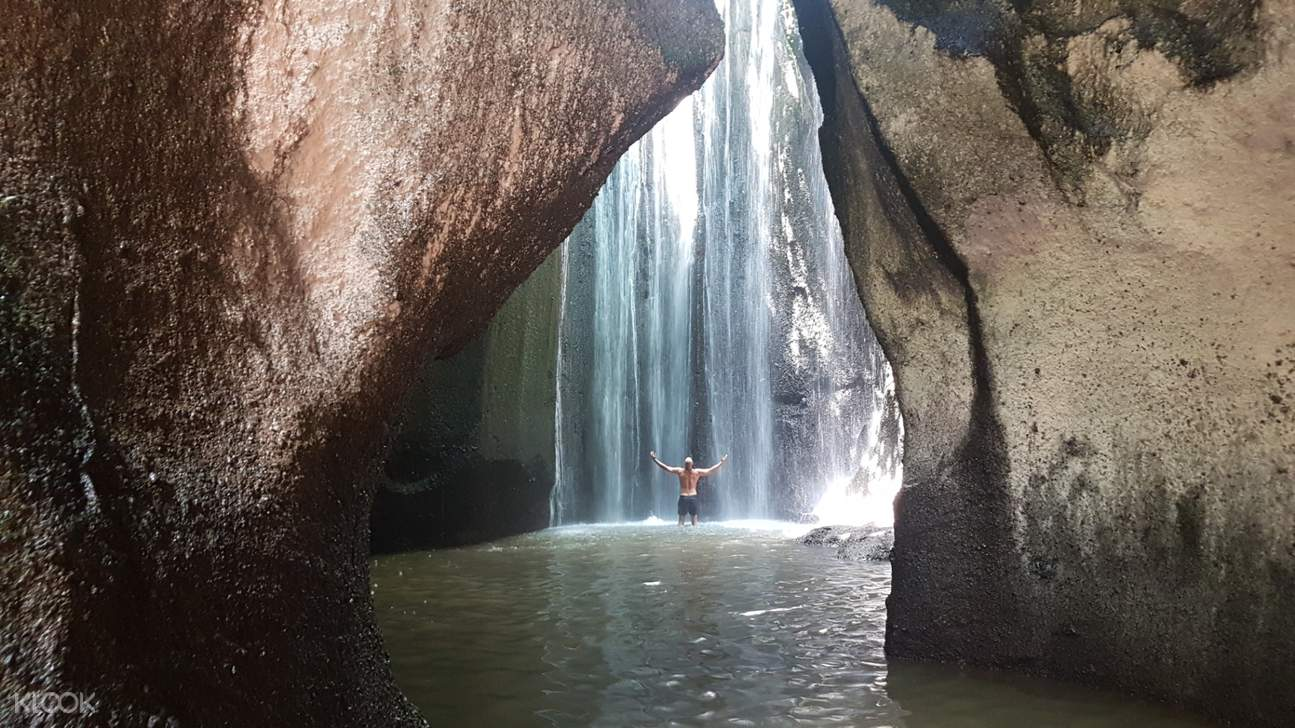 man in the middle of waterfalls in bali
