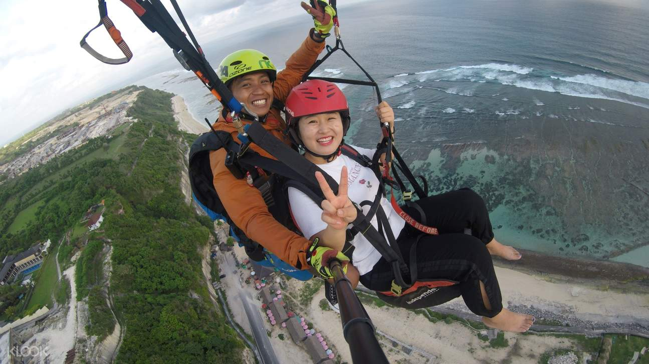 women taking a photo of herself while paragliding