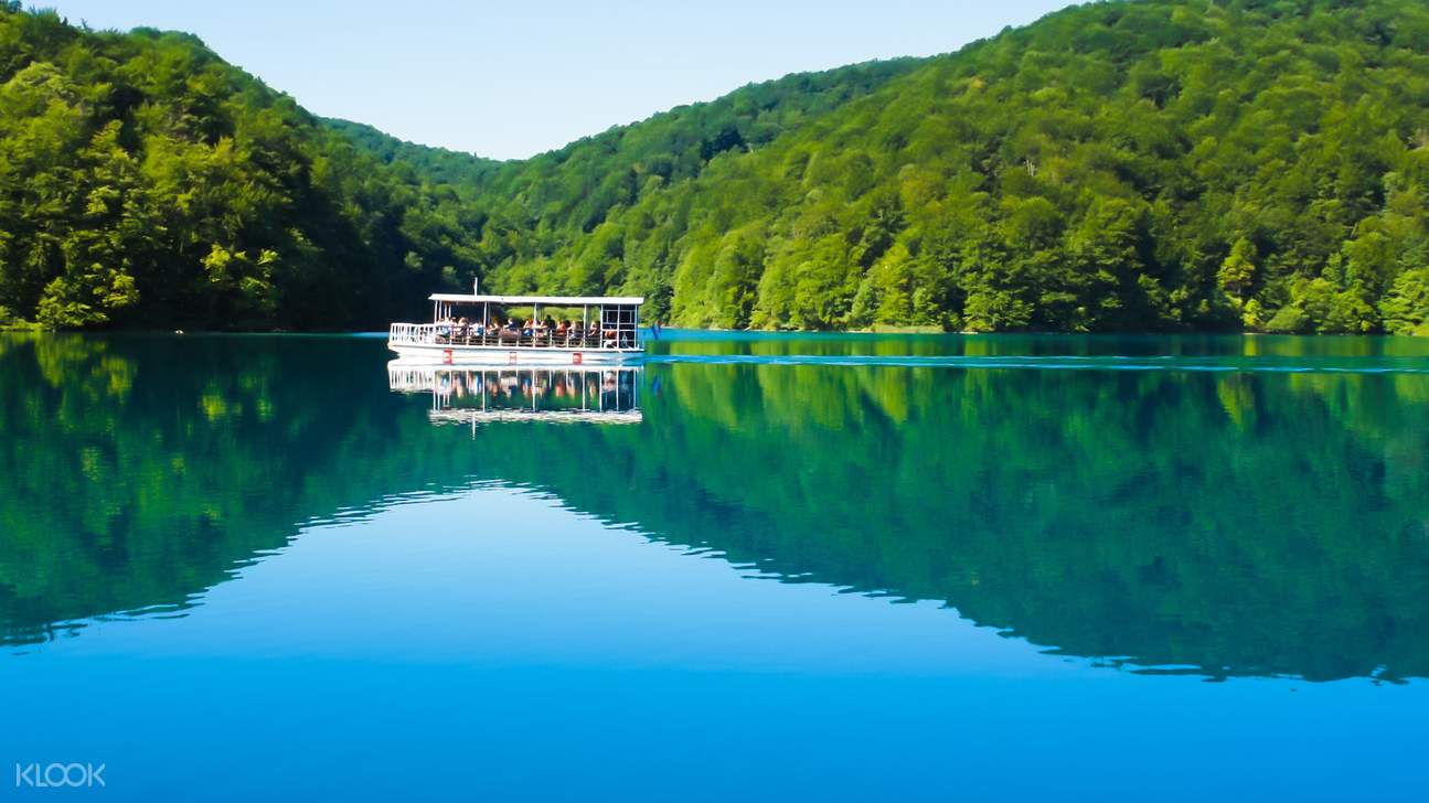 a boat cruising along one of the lakes in Plitvice Lakes National Park
