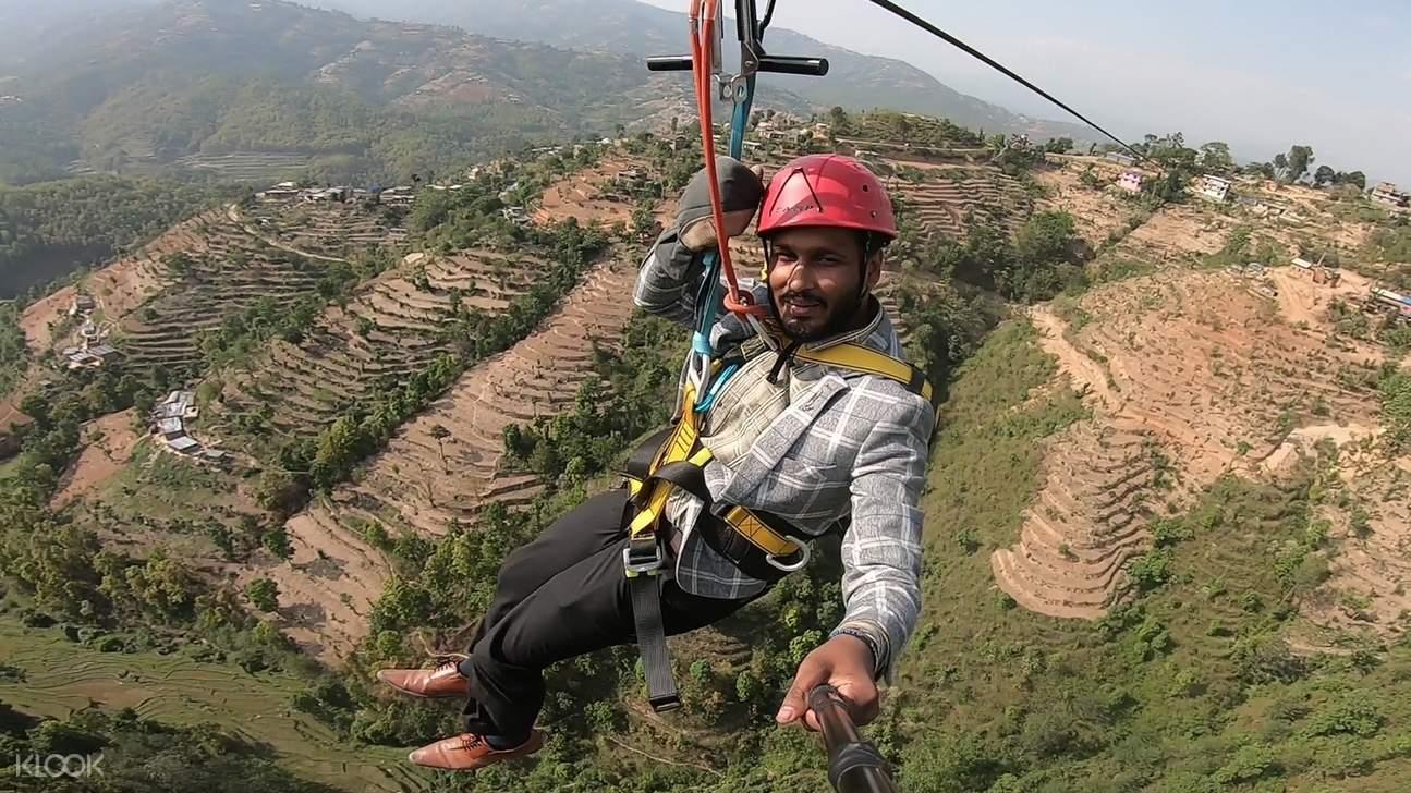man on zipline with views of rice terraces in Dhulikhel