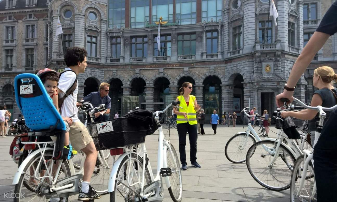 a group of people listening to a tour guide outside the Antwerp Central Station