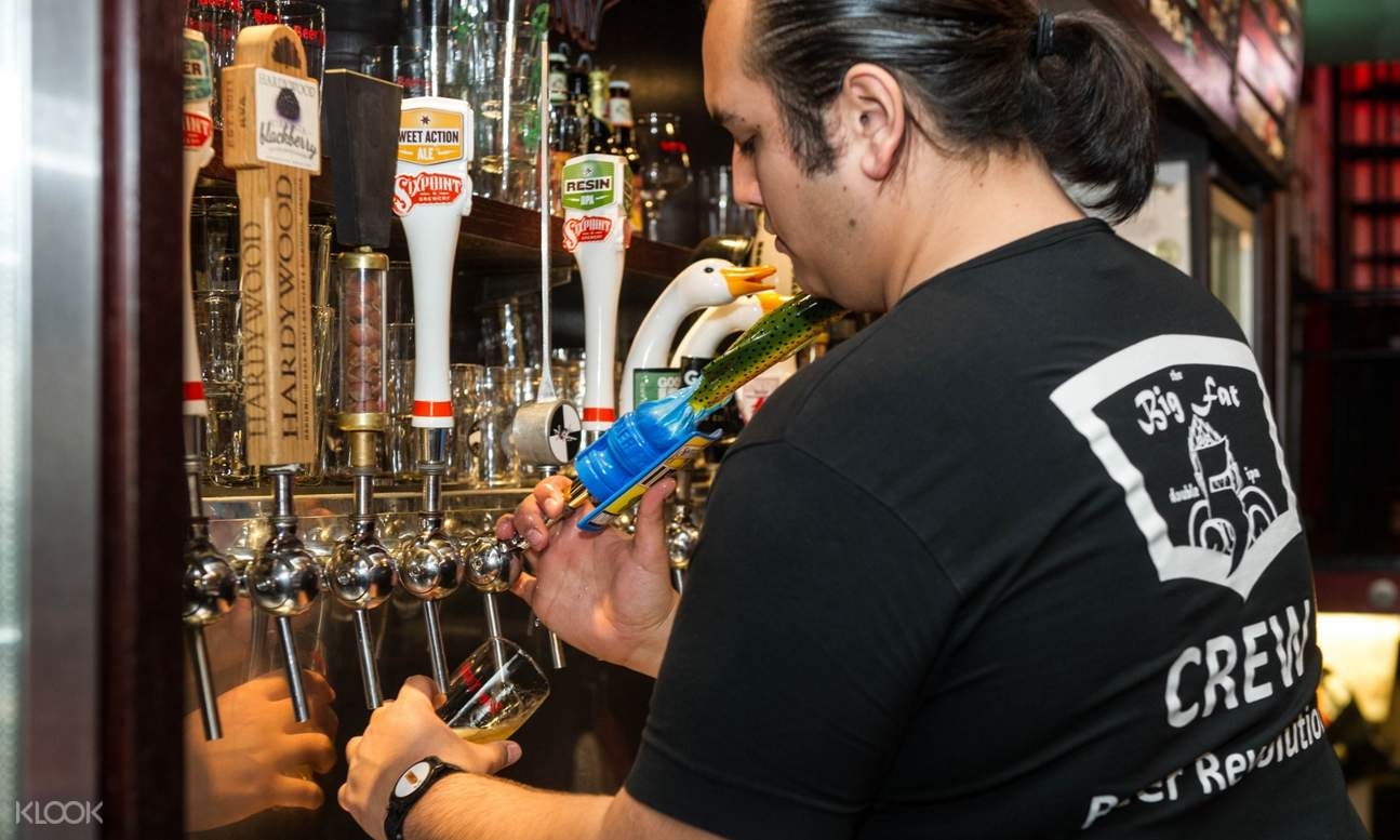 barista pouring beer into a glass