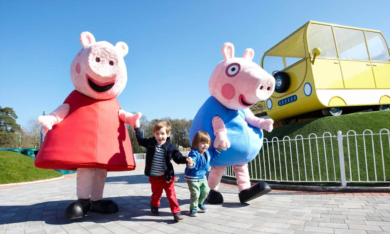 two kids walking with mascots in peppa pig world