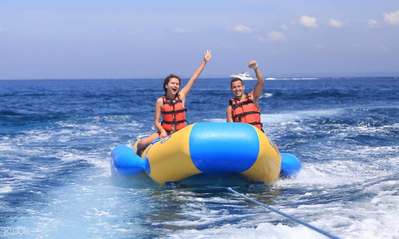 man and woman waving from a banana boat