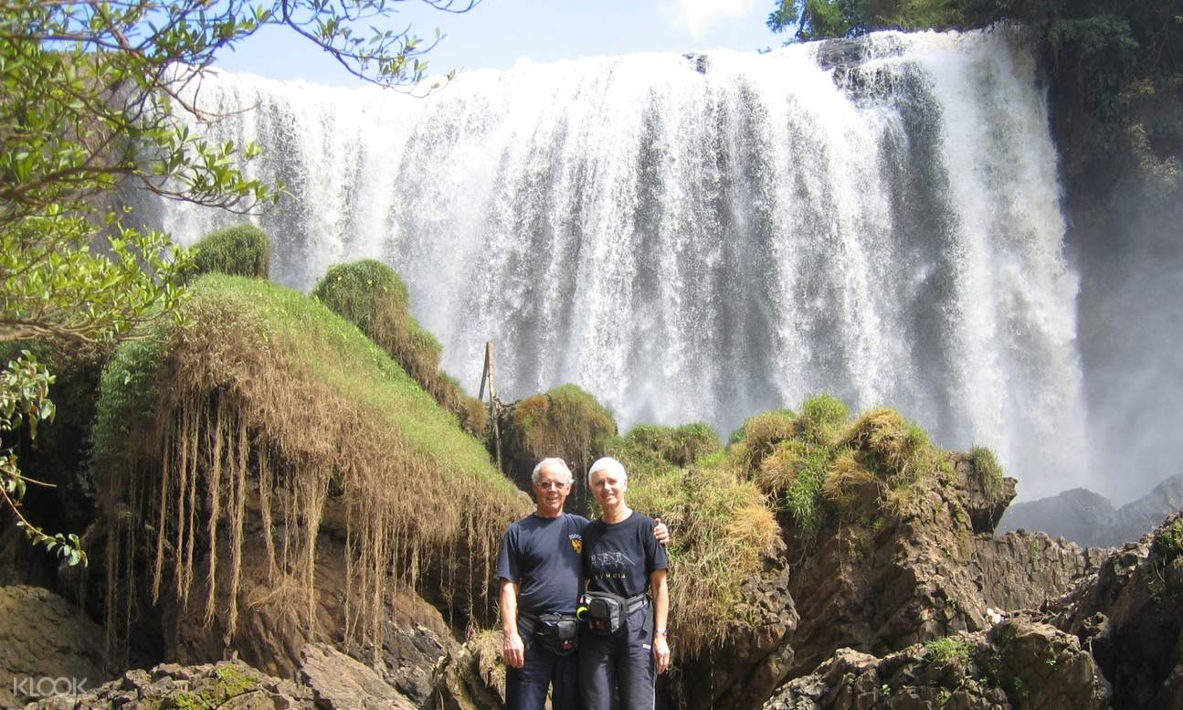 a couple taking a picture in front of waterfall
