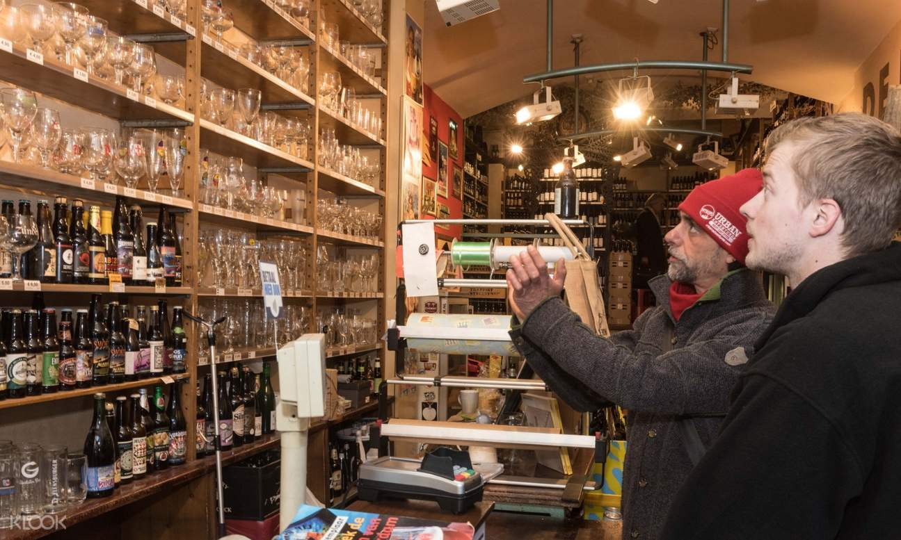 man and tour guide looking at a display of different beer glasses over history