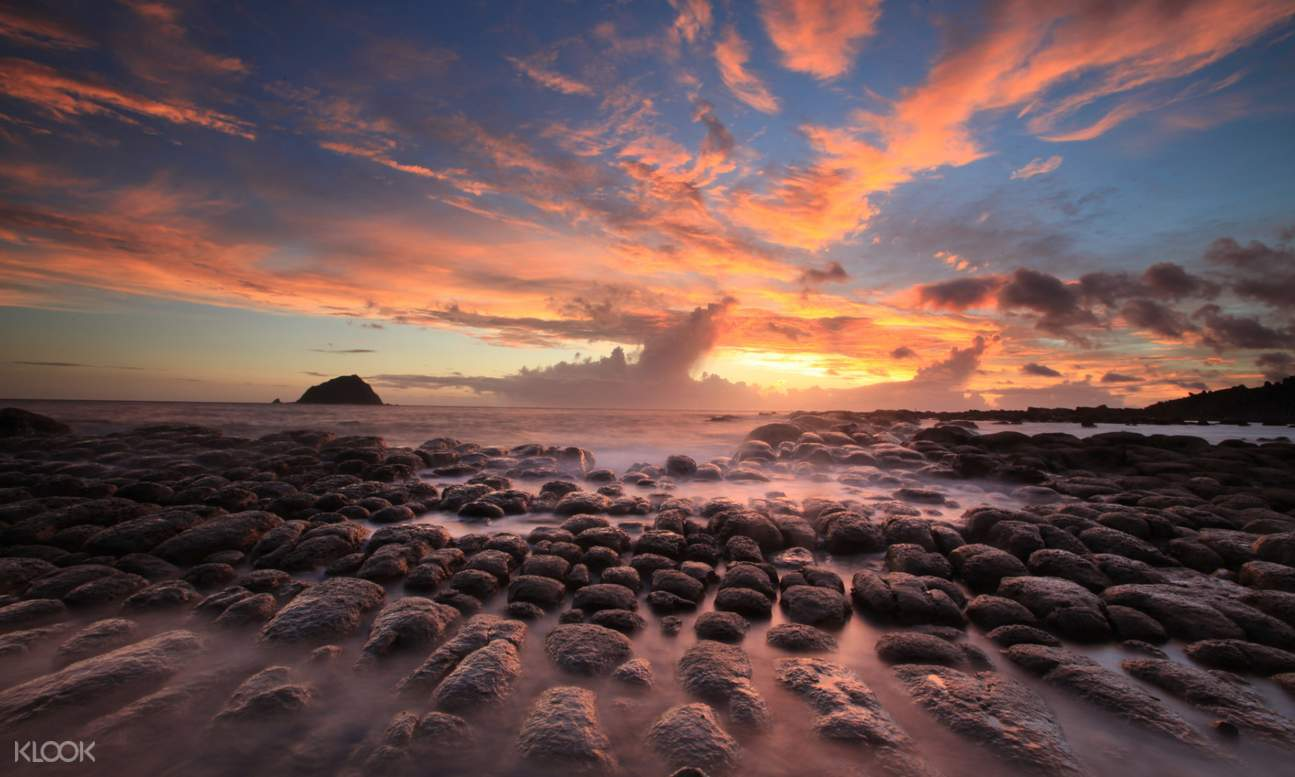 rocks on shallow water and view of the sunset