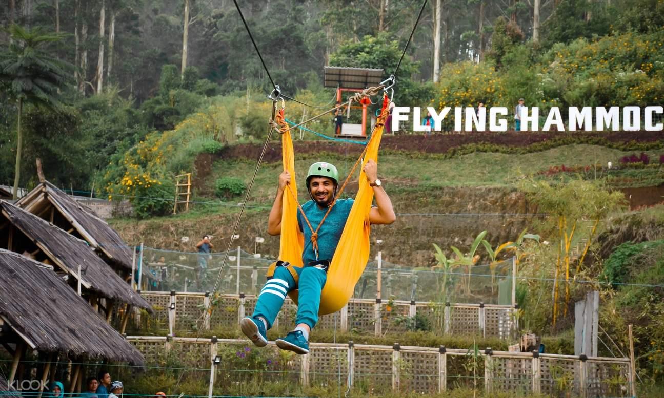 wisatawan naik flying hammock di dusun bambu