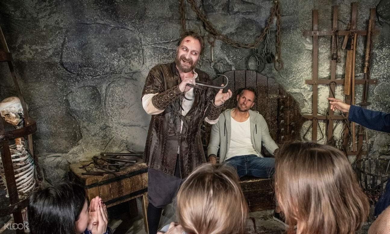 an actor in front of a crowd in the dungeon