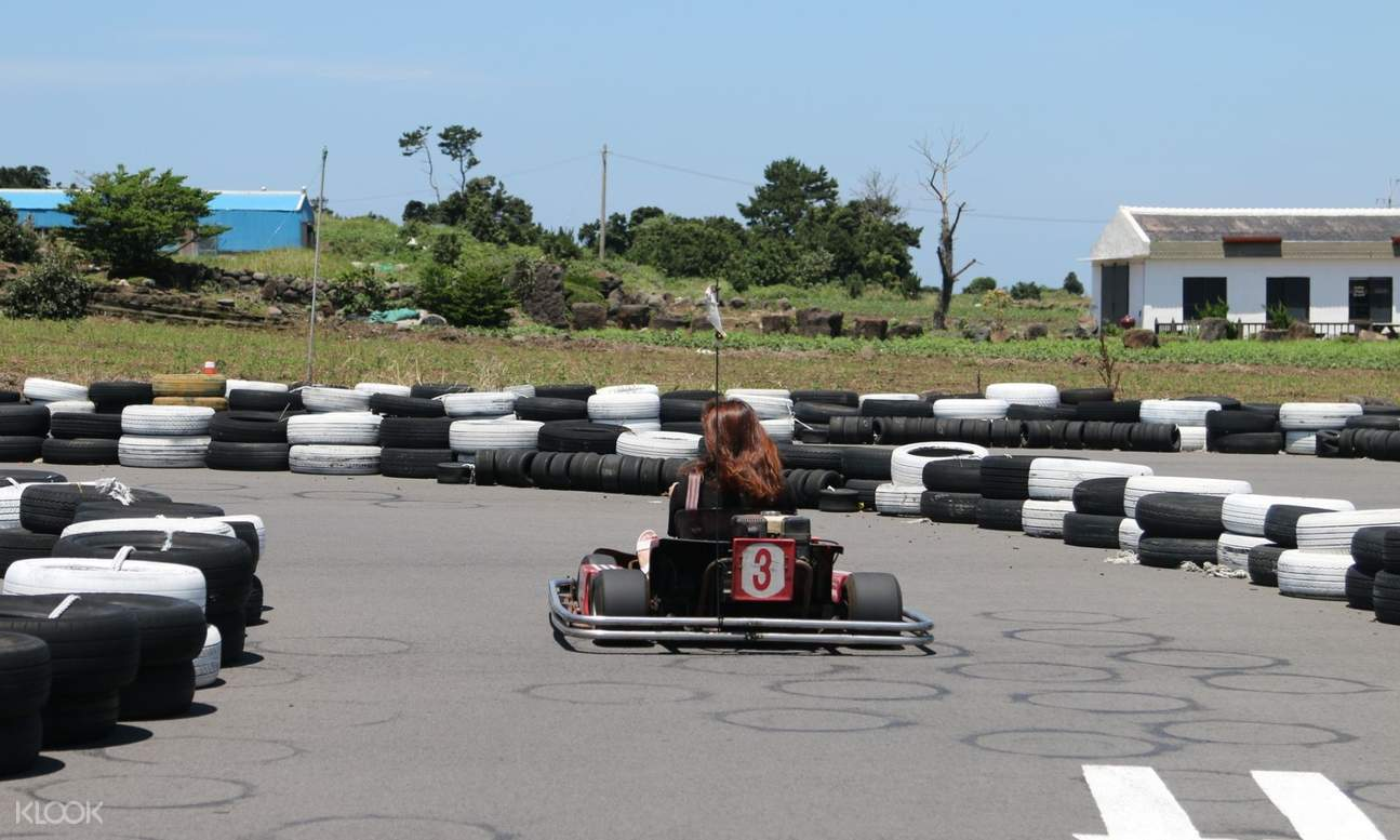 a woman riding a go kart about to take a turn