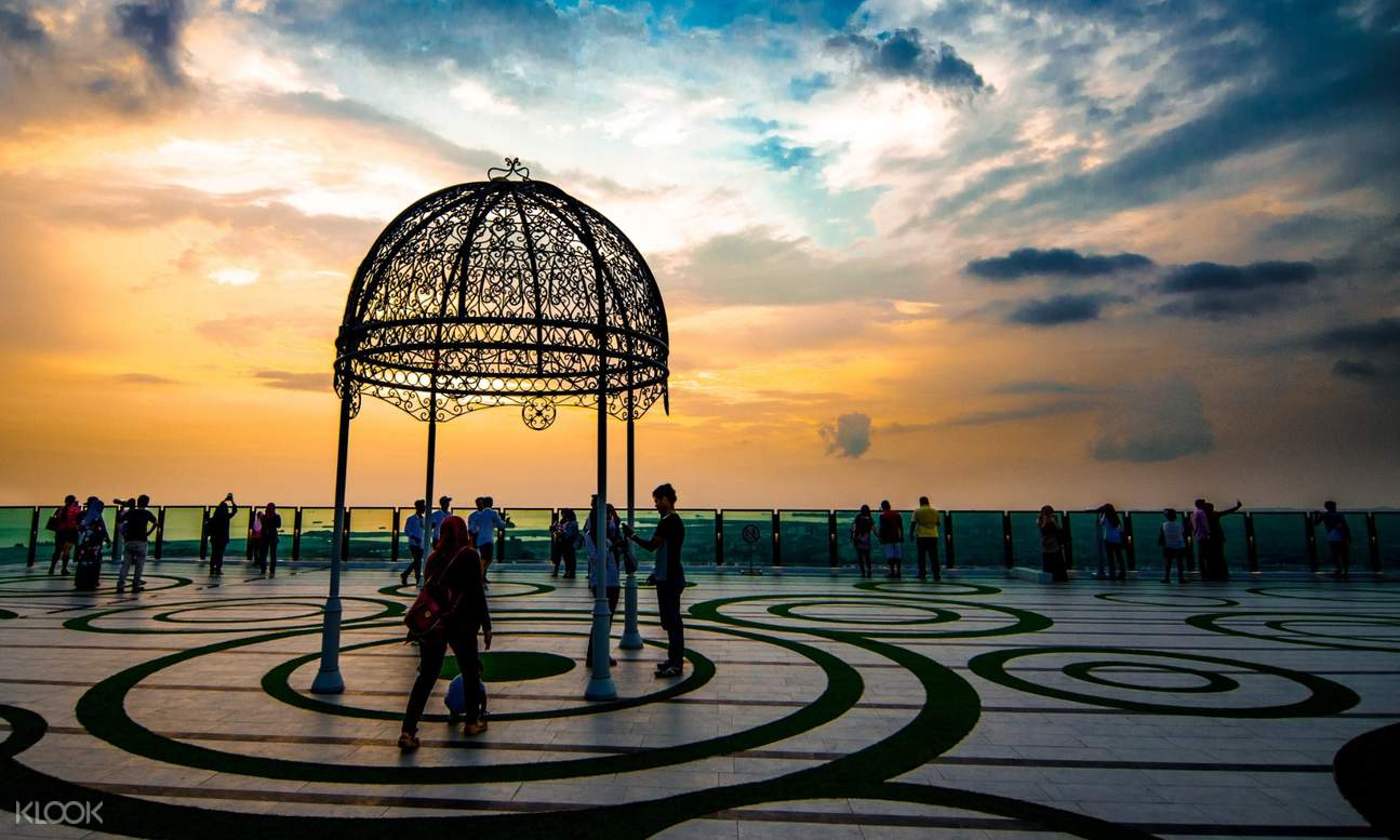 people and decorative structure on observation deck with sunset in the background