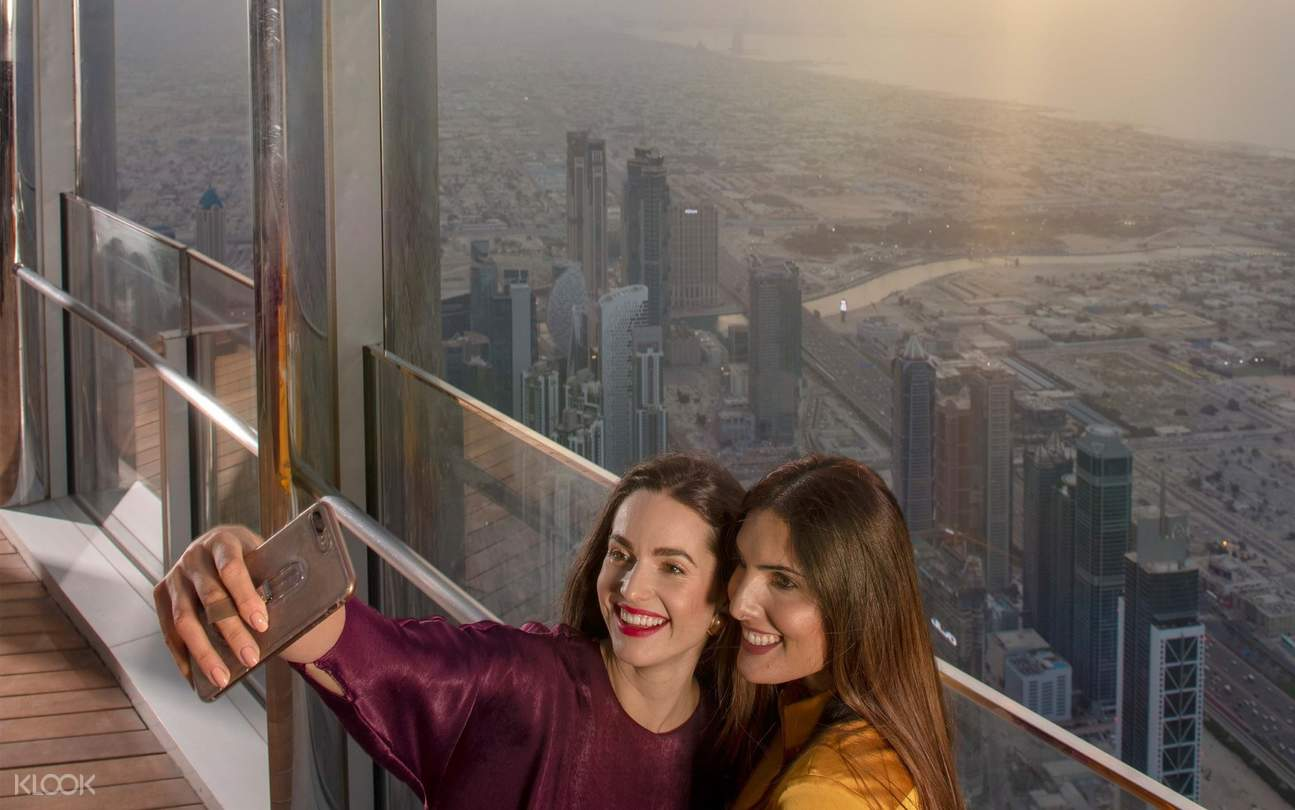 girls taking picture of city view from burj khalifa