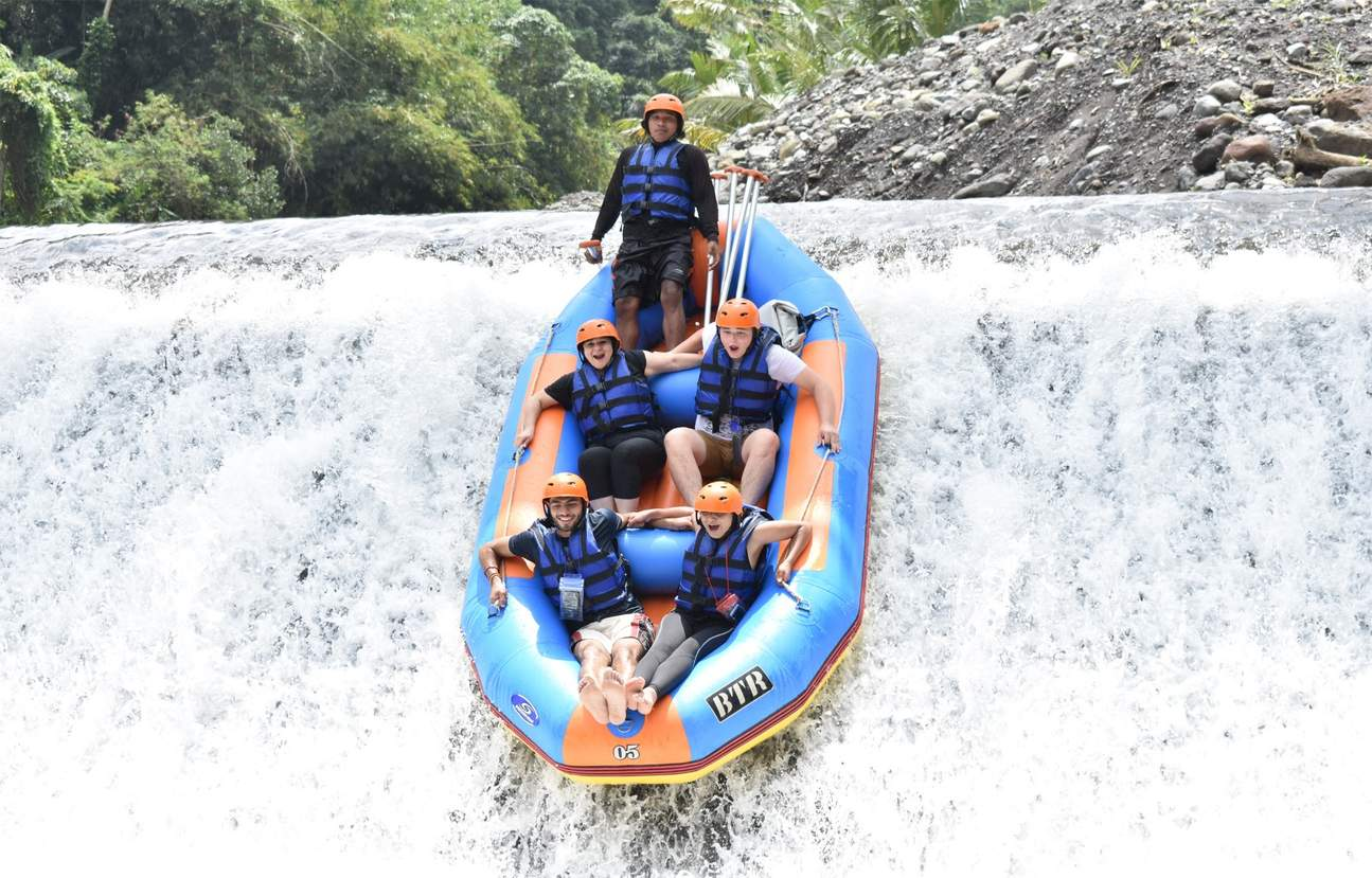 Group on raft sliding down waterfall