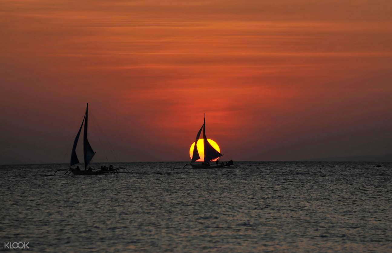 several sail boats in the sea during sunset