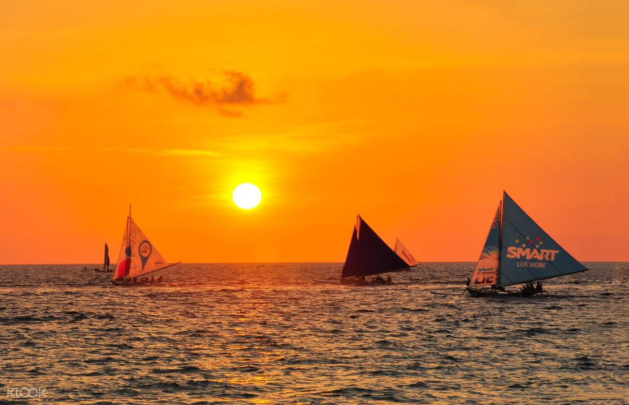 sunset in boracay with sail boats