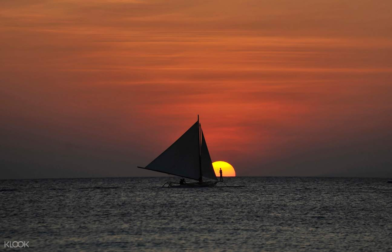 sunset in boracay with the sun and paraw boat