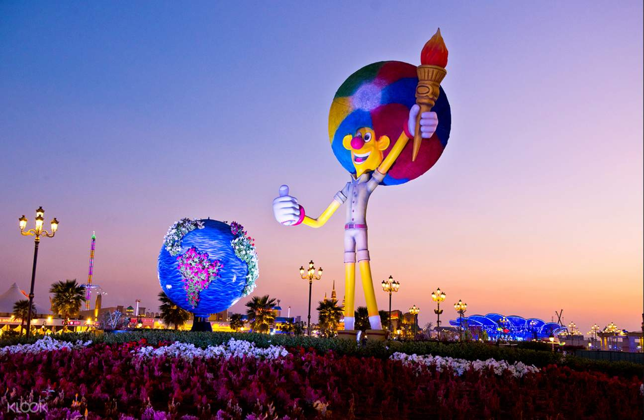 A large statue of global village mascot, a yellow skinned clown holding a torch
