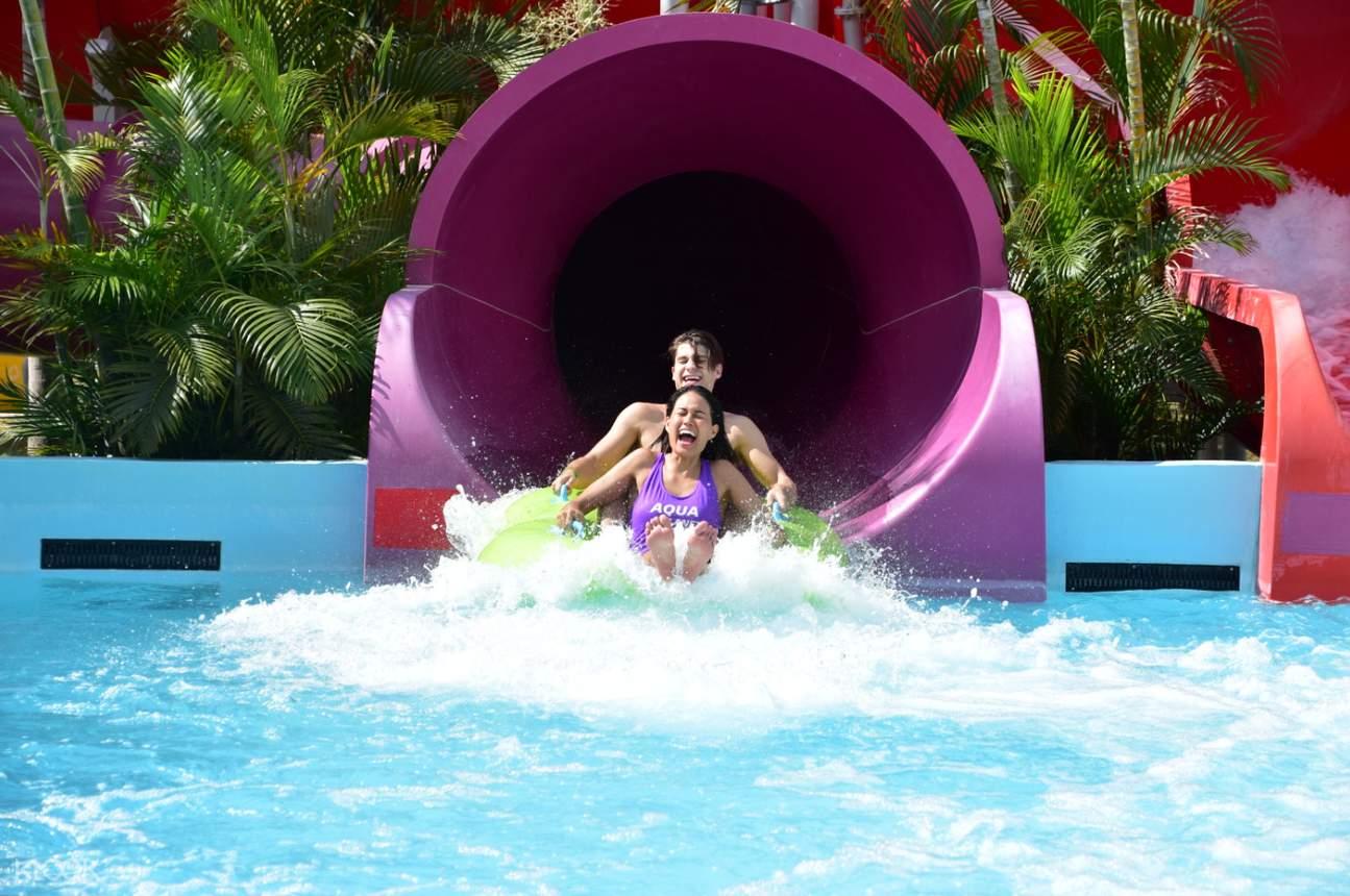man and woman sliding at aqua planet waterpark