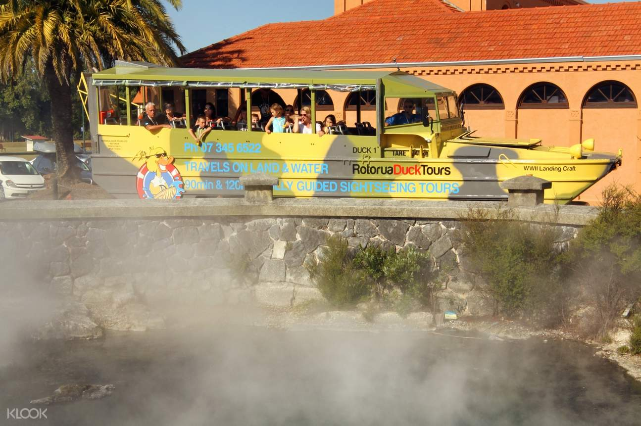 tourists on WW2 amphibious vehicle looking at hot springs
