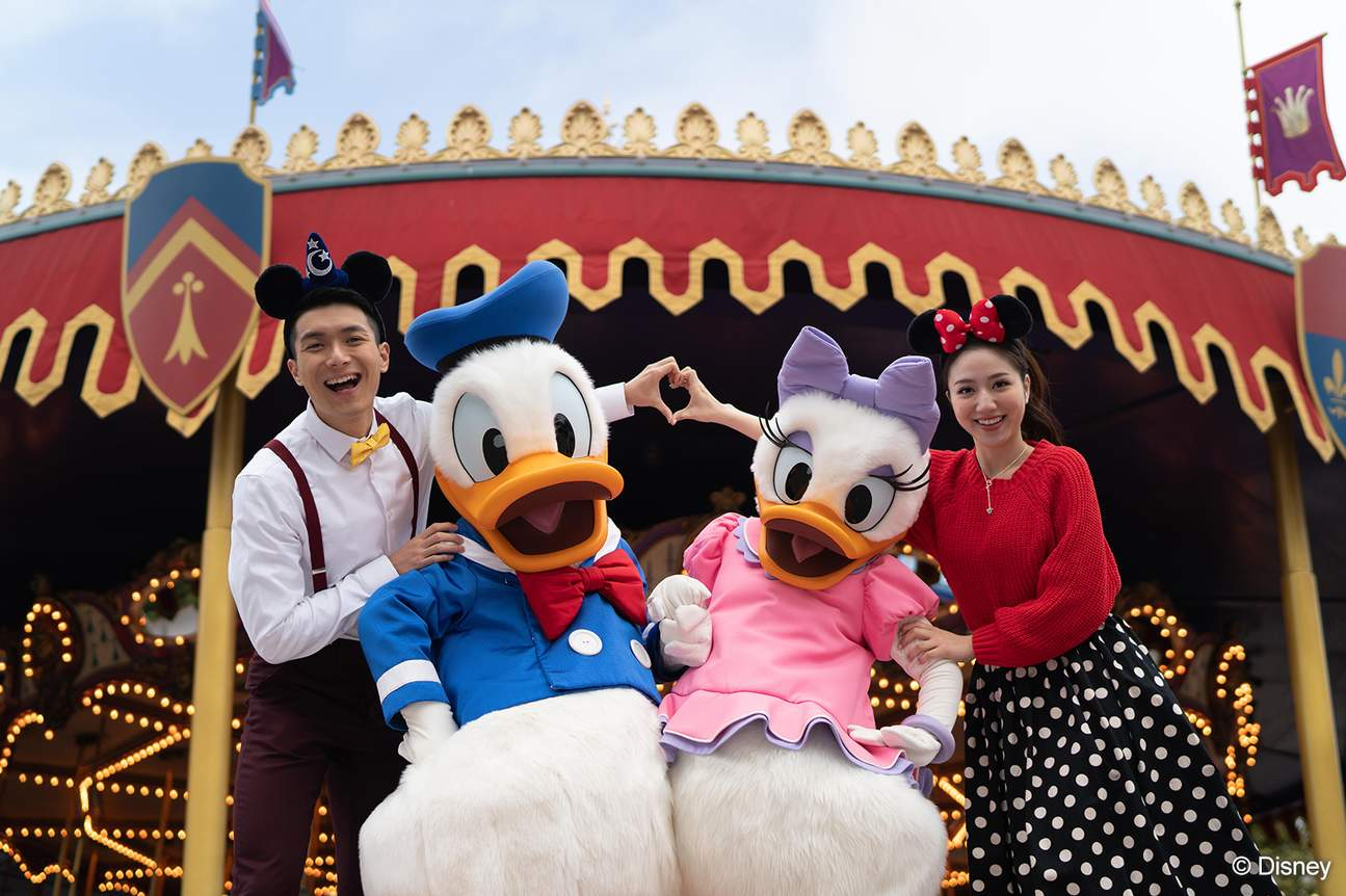 couple posing with Donald and Daisy Duck