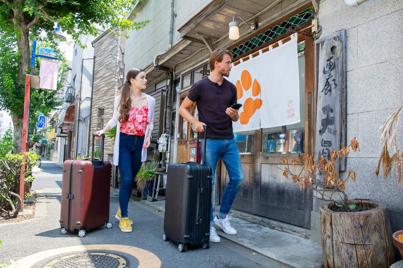 man and woman traveling with luggage