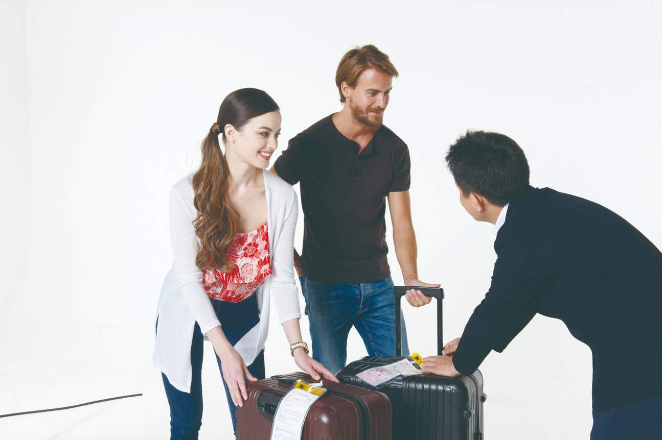 man and woman picking up luggage